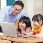 Man and two kids smiling looking at a computer screen